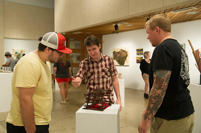 Students Laramie Fain(left), Jared Brandt and Wes Hennig critique an artwork done by Dan Heskamp in Student fall exhibition.