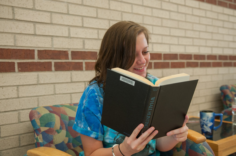 Hope Brookshire reading the history of whale hunting while waiting for her Chemistry class to begin.