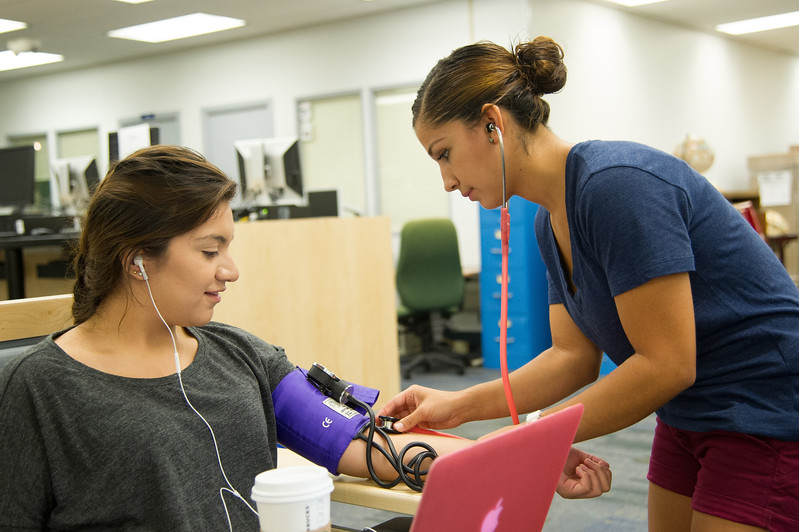 Jenny Ramirez check Ahtziri Gonzales' vitals for her nursing assignment in the Mary and Jeff Bell Library.
