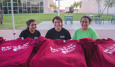 Students Sienna Gil (left), Julia Zuniga, and Charlcee Cervantez prepare to hand out t-shirts for CAB's 17th Annual Battle of the Bands.