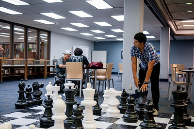 Life size chess game being put to use on the second floor of the Mary and Jeff Bell Library by Rojelio Hernandez.