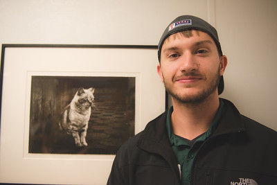 Zach Cobbs poses in front of his print for his photography class.
