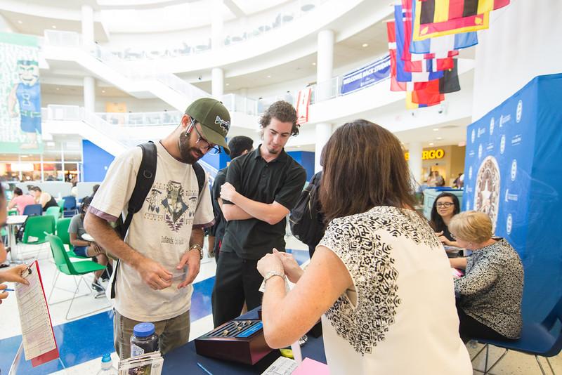 Daniel Knesek (left) and Juan Zepata purchase their Islander Ring in the UC.