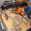 Students Ryne Ritterbach, Kevin Torres, and Brendan Villa take a break between classes to work on a 1,000 piece puzzel in the library.