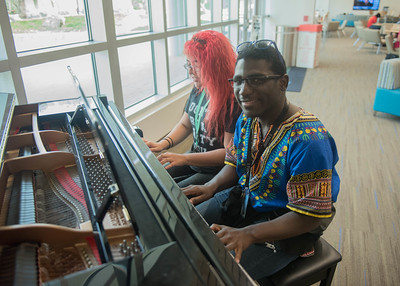 Students Damaris Sanchez and Theodore Woods-IV playing the piano in the Tejas Lounge.