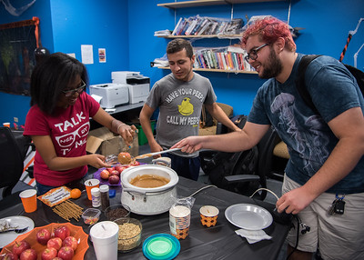 Students Samuel Guevara (far right) and Michael Martinez (middle) help student Shayla Frazier with a caramel apple at the Honors Program Open House event.