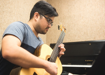 Student Michael Maceda performs on his guitar in the Center for the Arts practice rooms.