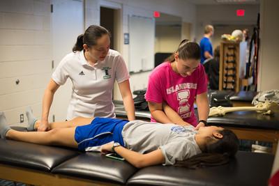 Clinical professor Sayuri Hiraishi observes student Amanda Clark as she demonstrates a shoulder analysis on fellow student Kimberly Montez.