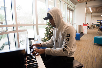 Student Jared Alvarado plays the piano in the UC Tejas Lounge.