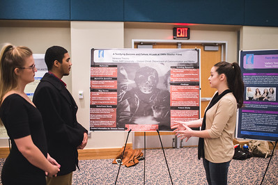 Student Vanessa Trevino (right) explains the success of early slasher films for her Senior Seminar communications project in the University Center.