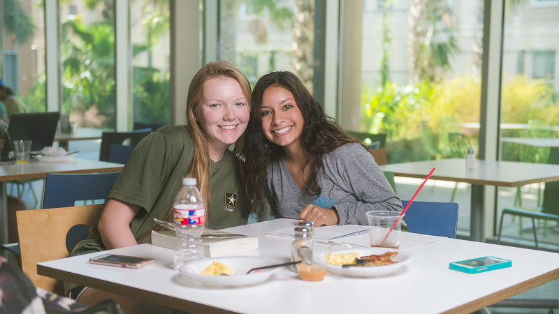 Alyssa Metts and Destiny Arocio smile for a photo while catching up on schoolwork over lunch in the Texas A&M Corpus Christi Islander Dining Hall.