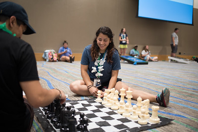 Macro Valdez (left) assist Alyssa Espinoza on the rules of chess. As they wait for the Aloha Days event to begin.