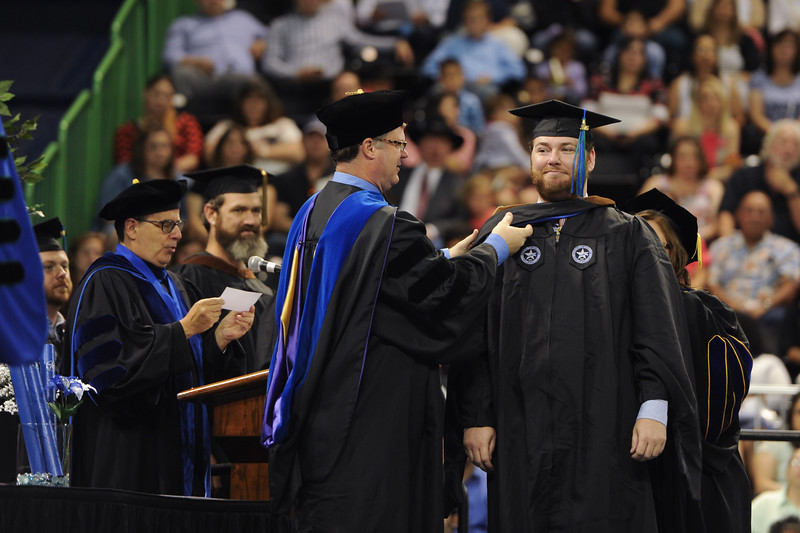 Tyler Barner receives is hooded by the Dean of CoLA Dr. Hartlaub during the 2016 Commencement ceremony.