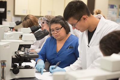 Professor Sella Doyungan assists Lorenzo Garcia with the micro biology lab.