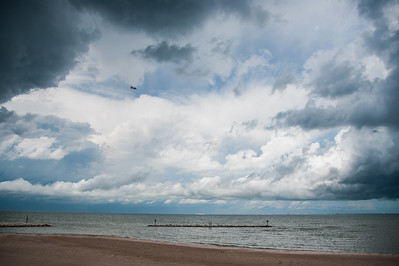 Dark clouds envolop the sky as a plane passes the university beach.
