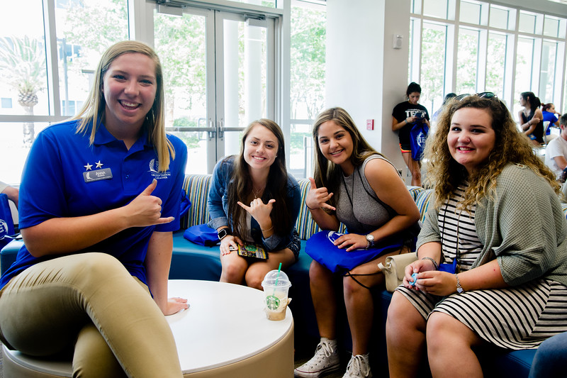 Orientation leader Anna Norris poses for a photo with orientation guests in the Tejas Lounge.