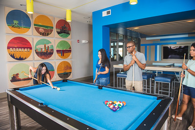 Brittany Uresti (left) Isabel Zapata, Sterlen Kemp and Andrea Gilson start a round of pool at the Momentum Village apartments.