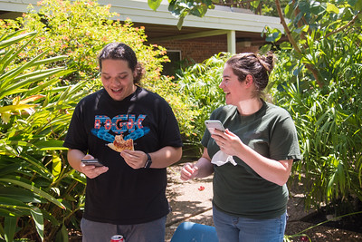 Level 15 Pokemon trainer, Joe Hernandez (left) and Level 10 trainer Rachel Bennett enjoy free piza from PASS as they catch and tame wild pokemon outside of the CASA building.