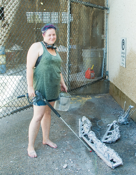 MFA student Nicole Scunnell works on pressure washing her sculpture.
