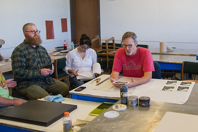 Professor Rich Gere reviews prints with his Lithography class.