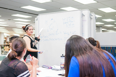 Student Keila Flores demonstrates an equation from her Biomechanics class to her peers in the Mary and Jeff Bell Library.