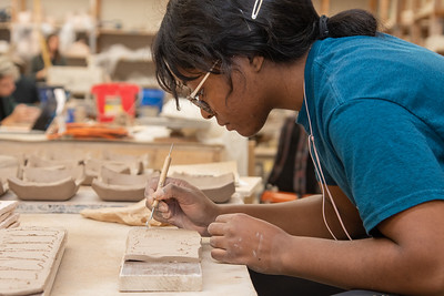 Christine Anusim working on her ceramic teeth ornaments in the Center for the Arts.