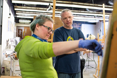 """Angela Resendez (left) receives feedback from Professor David Hill as she continues to work through her """"There's No Earth Way of Knowing"""" portrait piece for Intermediate Painting."""
