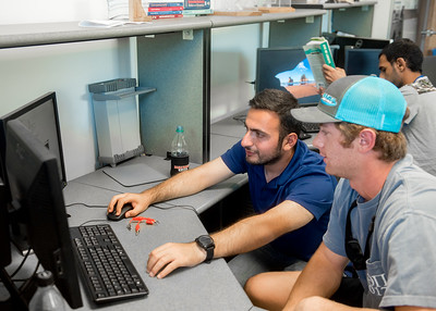 Teaching assistant Mehmet Ozkan (left) helps student Jerry Shea run the process of comparing data between gears during a lab session of Engineering Measurements.