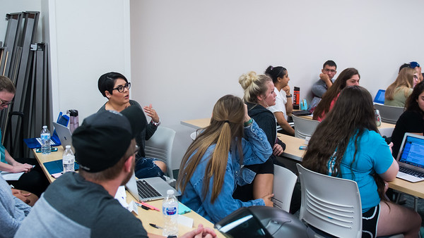 Students discuss feedback between people during their Professional Nursing Issues I class.