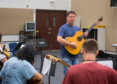 Professor Michael Moore demonstrates to his class how to play harmonics in Basic Guitar I.