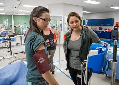 Students Rachel Kasowski (left) and Julianna Benitez prepare for their nursing final exam by practicing a simulation.