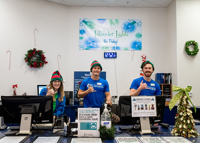 Student workers Anna Bachman (left), Daniel Stacy, and Connor Flynn show off their Islander spirit and holiday joy in the Dugan Wellness Center.