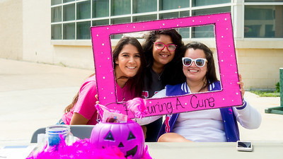 Sofia Flores (left), Brittany Trevino, and Maddy Hernandez set up a table on the East Lawn to promote Breast Cancer Awareness Month.