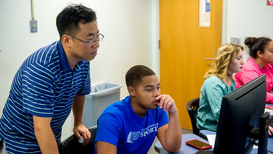 Professor Taewon Lee (left) assists student Larry Gibson on his exercise in Statistics for Life assignment.