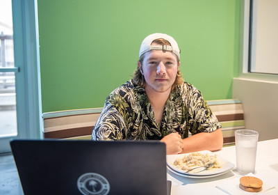 Joshua Robinson Bayless catches a bite after class at the Dining Hall as he watches his favorite show.