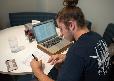 Nick Newman works on his Philosophy assignment at the Dining Hall between classes.