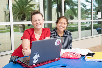 Students Jolea Pogne (left) and Angelene Cook catch up on their political science studies in Anchor Plaza.