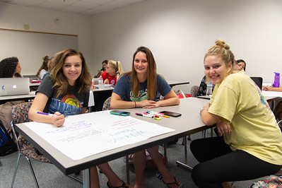 Kara Bartlett (left), Mary Ross, and Amanda House work together on a memory poster for their Childhood Development course.