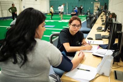 Amber Hargens (left) checks student Erica Rios blood pressure before undergoing the various Kinesiology fitness lab tests.