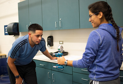 Ulisess Trajo (left) takes note of Kimberly Montie's dynamometer  hand grip for Kinesiology fitness test lab.