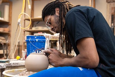 Joshua Williams throws a bowl on the wheel for his ceramic project in the Center for the Arts.