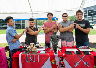 Members of Omega Delta Phi provide information about their fraternity during the Multicultural Greek Council Fall Festival.
