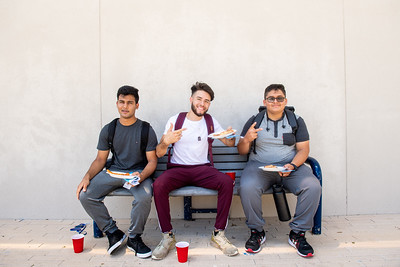 Students grab a slice of pizza during a Waves of Welcome event.