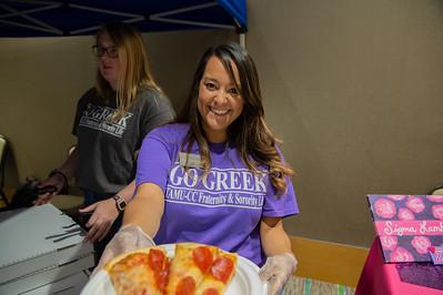 Staff hands out free pizza during the aloha org fest  for TAMUCC greek life.
