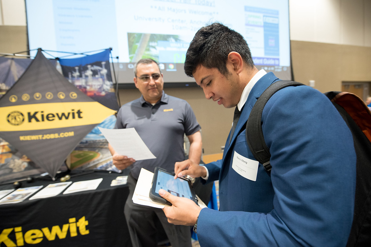 Student Mario Wong receives information about Kiewit job opportunities during the Career Fair in the University Center.