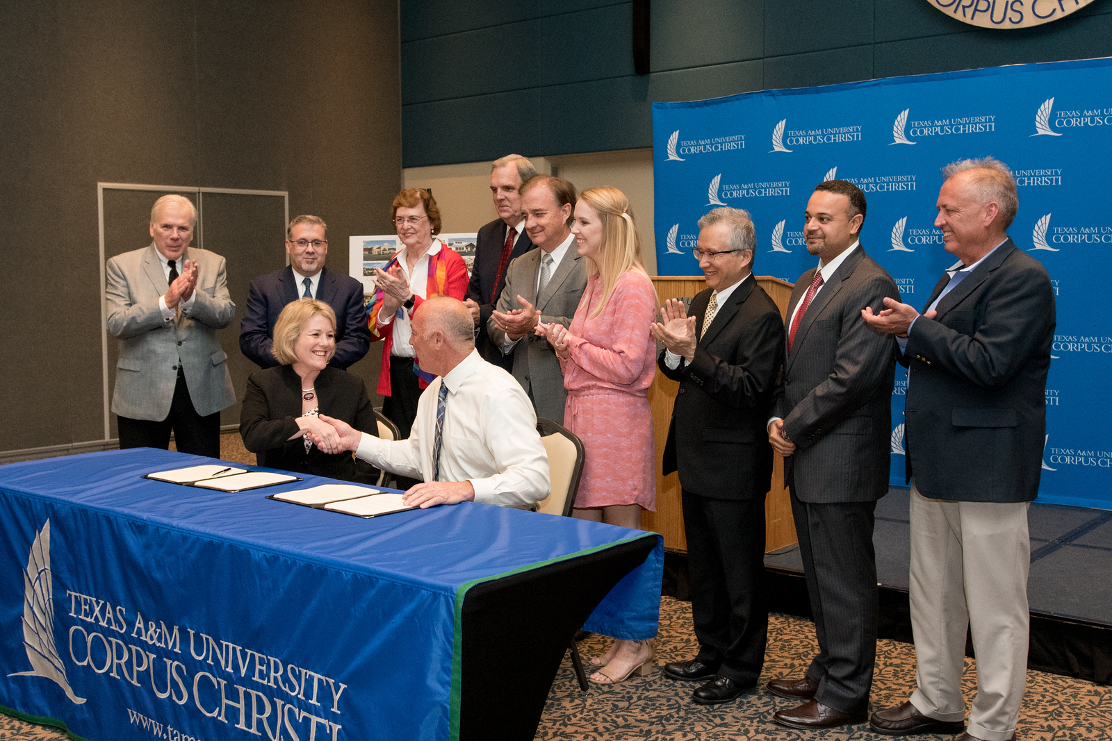 Interim President Kelly Quintanilla and Robert Johnson shake hands as dignitaries look on during the Innovative Aging Initiative Memorandum of Agreement Signing on Wednesday, March 22, 2017.