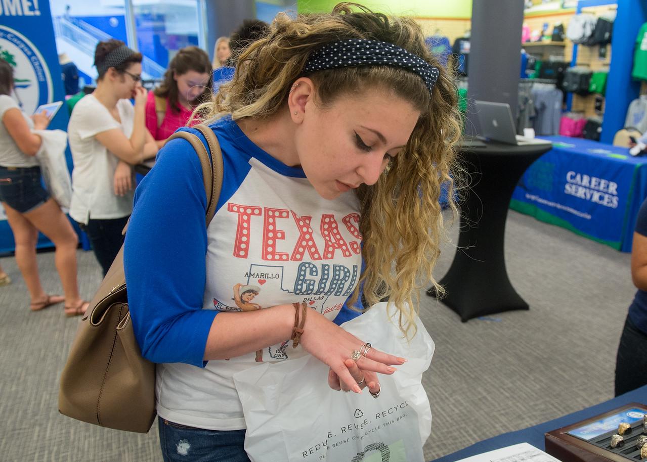 Sara Stephenson looks at class rings during the Spring 2017 Islander Grad Fair.