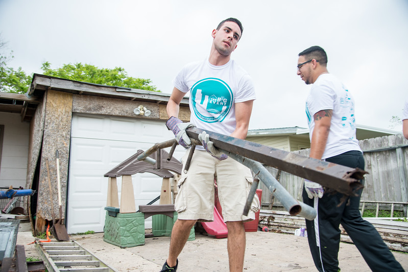 "Student volunteers help clear metal objects from a private property during Student Volunteer Connection's ""Big Event""."
