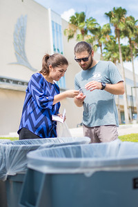 Megan Greige (left) assists Ben Ireland with sorting his recyclables.