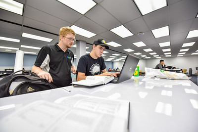 Austin Burkland and Gus Ladwig collaborate on their assignments in the Mary Jeff and Bell Library.
